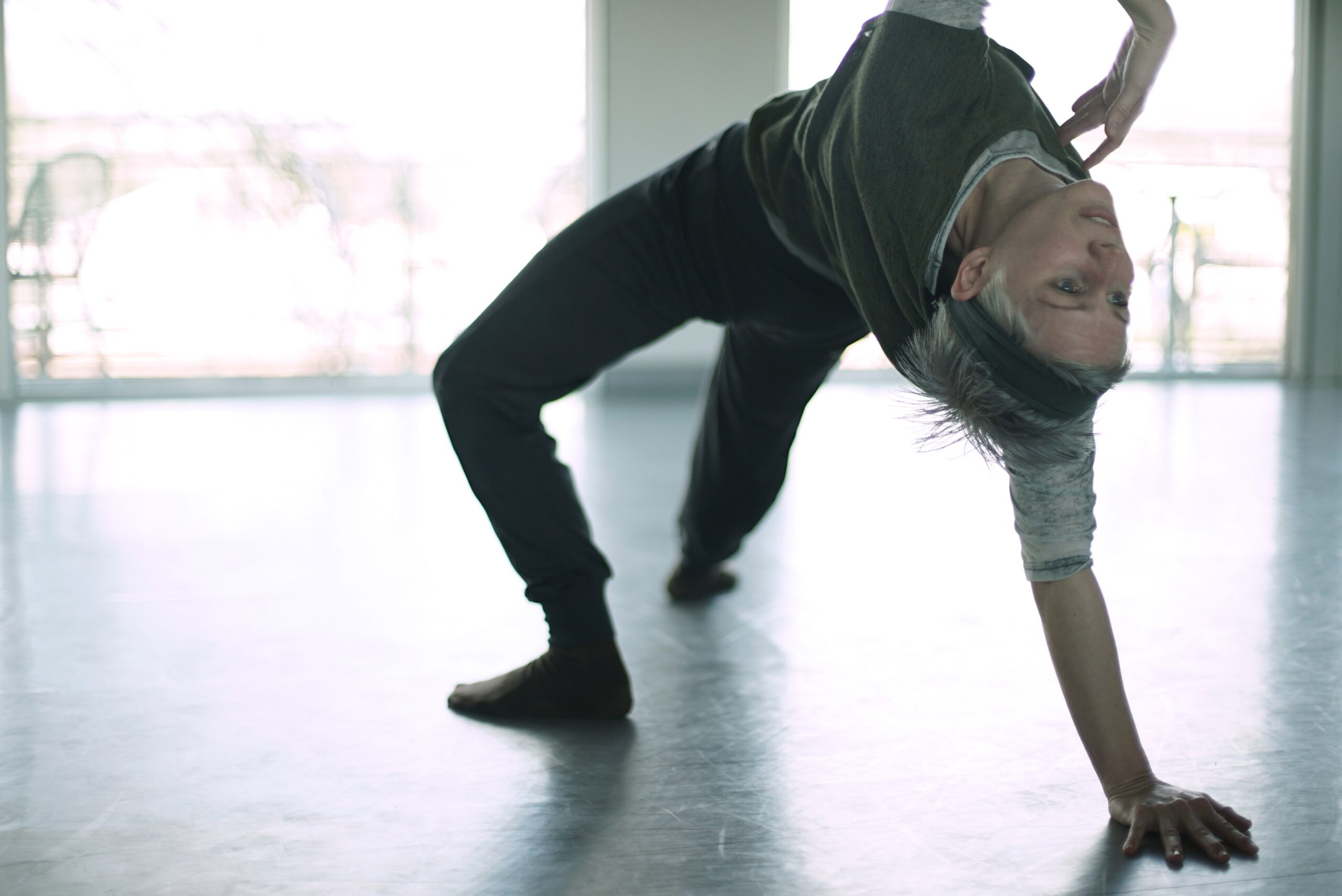 A dancer holds a sort of bridge pose in a dance studio, looking back and upside down