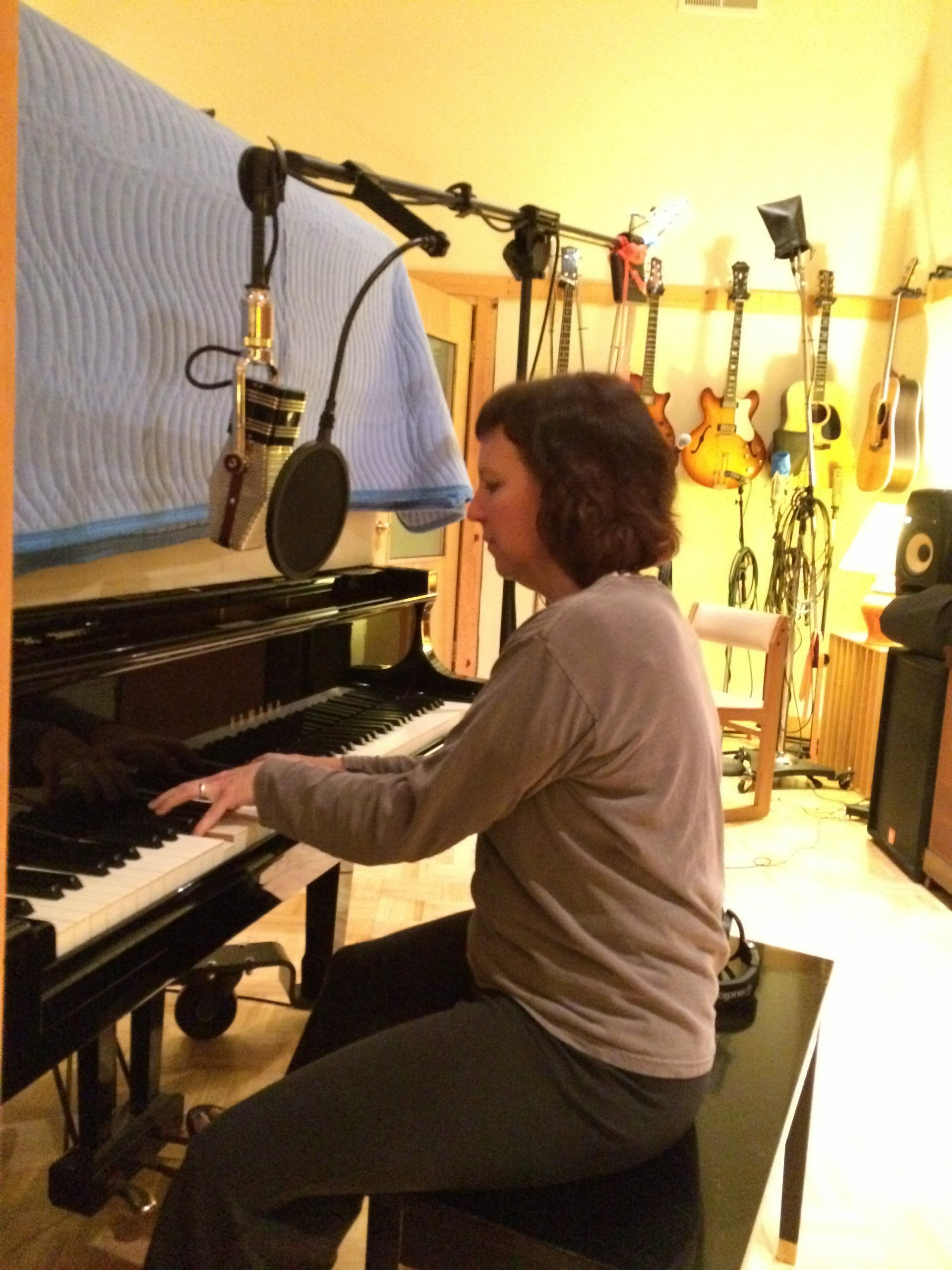 A musician plays a piano in a music studio