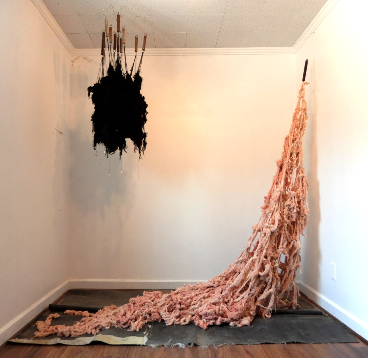 Installation art: A large clump of black fibre hangs from the ceiling and another fibre tangly mess hangs from the wall and drapes on the floor