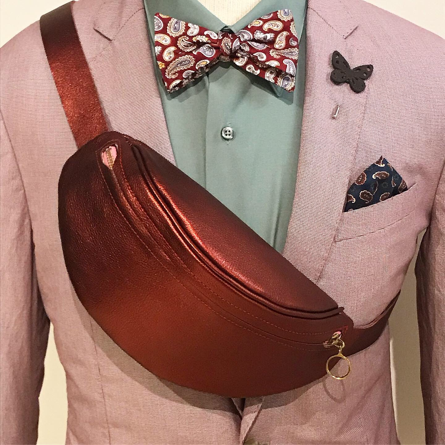 Closeup of a cross-body bag on a mannequin wearing a suit and bowtie
