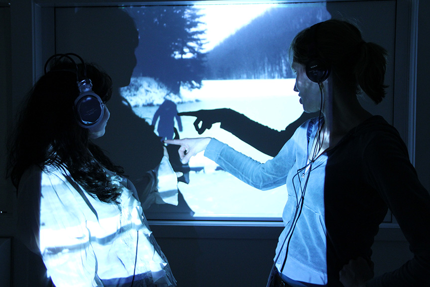 Two people stand in front of a projected image of a figure in a landscape. They are both wearing headphone and both turn around and point at the figure in the image
