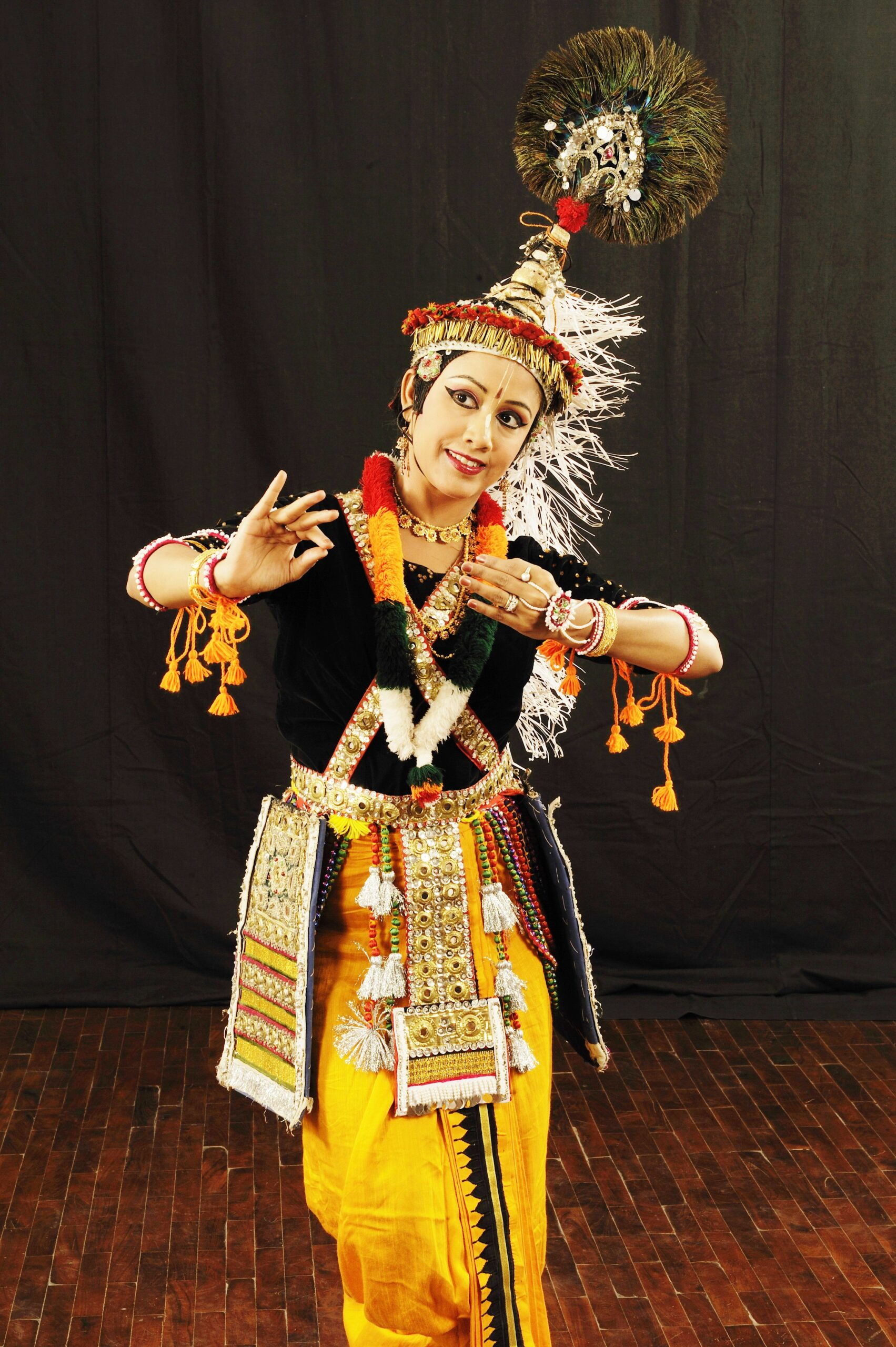 A dancer poses dressed in elaborate, bright traditional Indian costuming