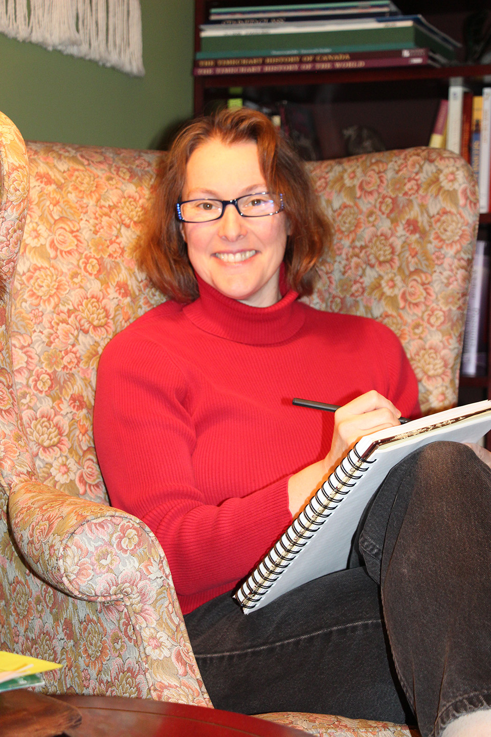 A woman sits in a wingback chair with a pen and notebook smiling at the camera