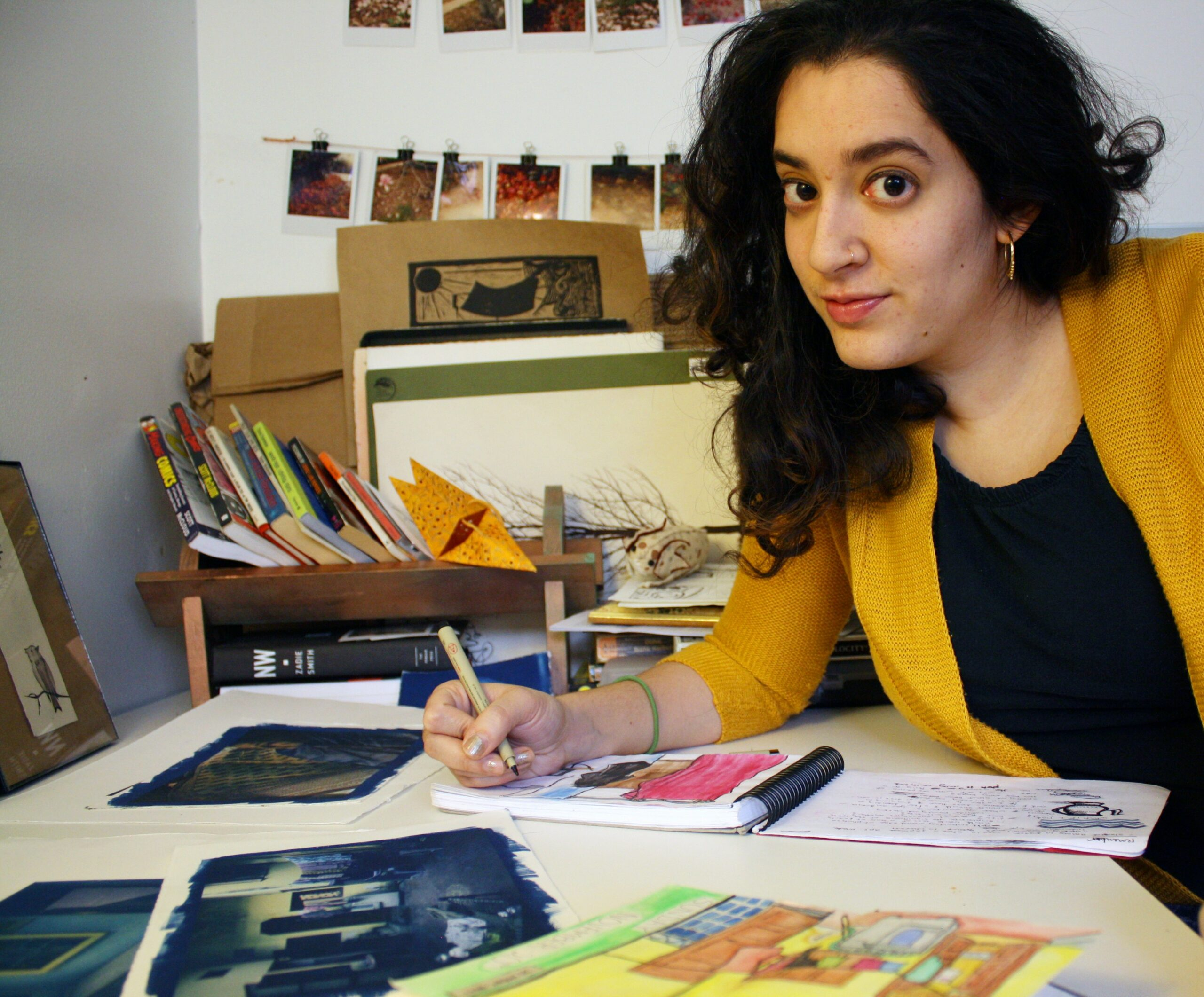 An artist draws with a pen on an open page in her sketchbook. There are books, sketches and polaroid pictures around her