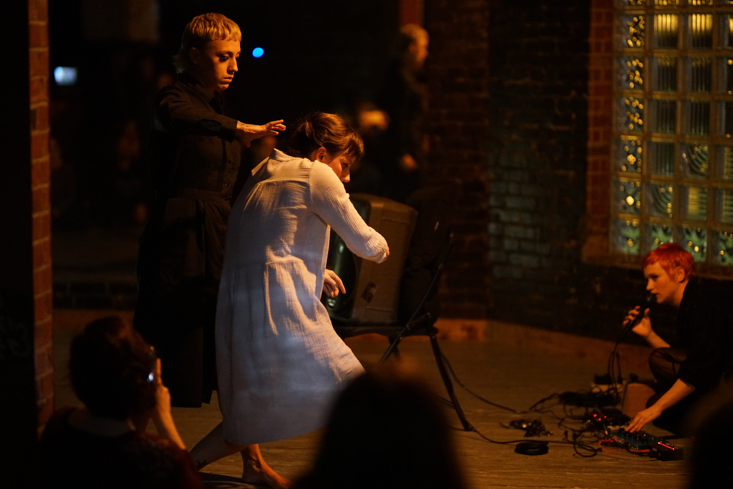 Three artists take part in performance art in a dark space. One person wears white and the other two wear black. One of the artists in black speaks into a microphone