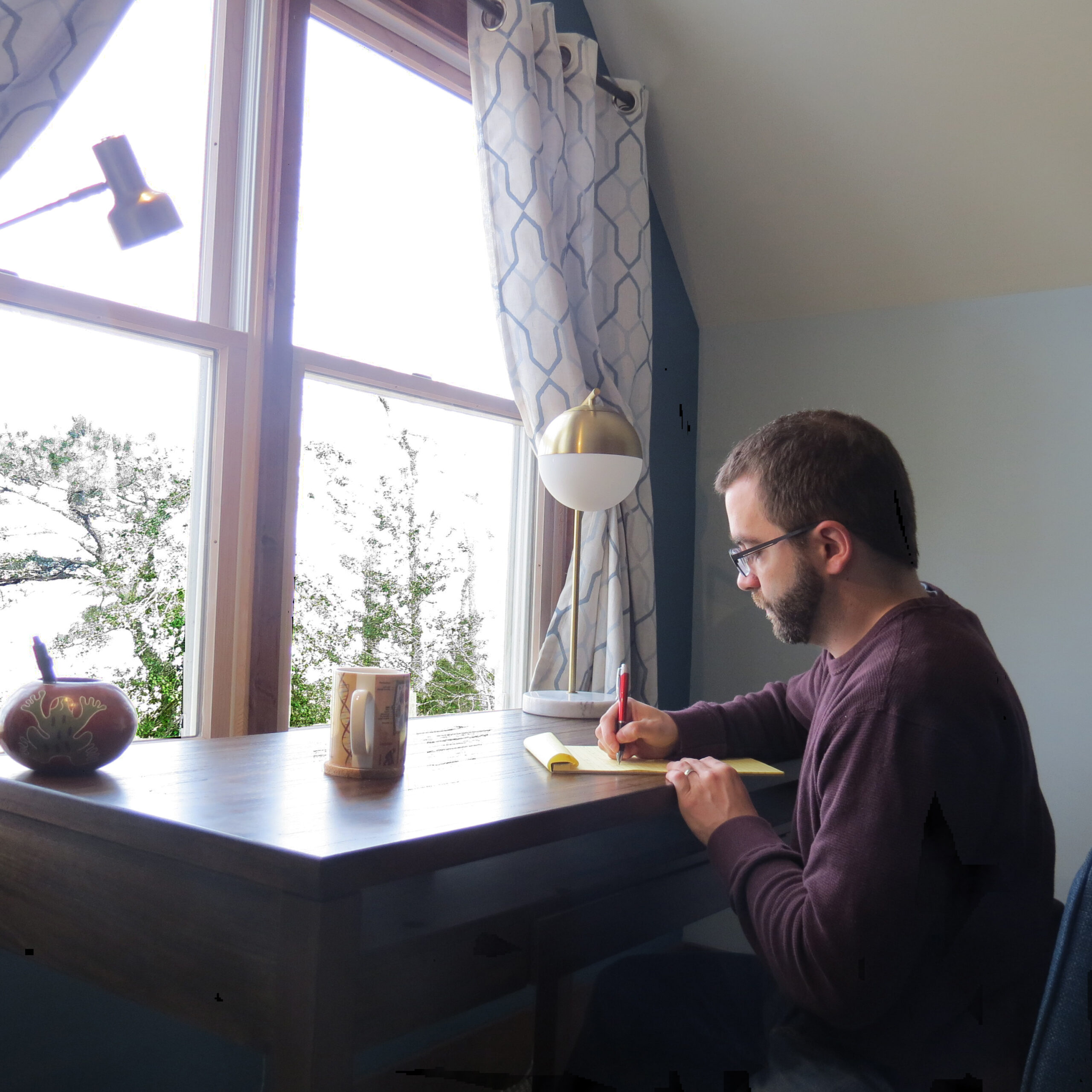 A man writes at a desk in front of a window