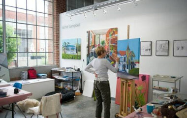 A woman works on a painting in an art studio with a large window in the background