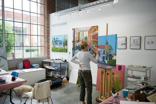 An artist works on a painting of a building in an art studio