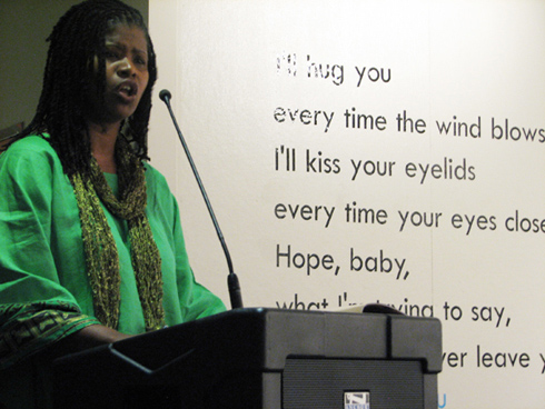 "A woman stands at a pedestal speaking into a microphone. Text visible on the wall behind her reads ""I'll hug you / every time the wind blows / I'll kiss your eyelids / every time your eyes close / Hope, baby"""