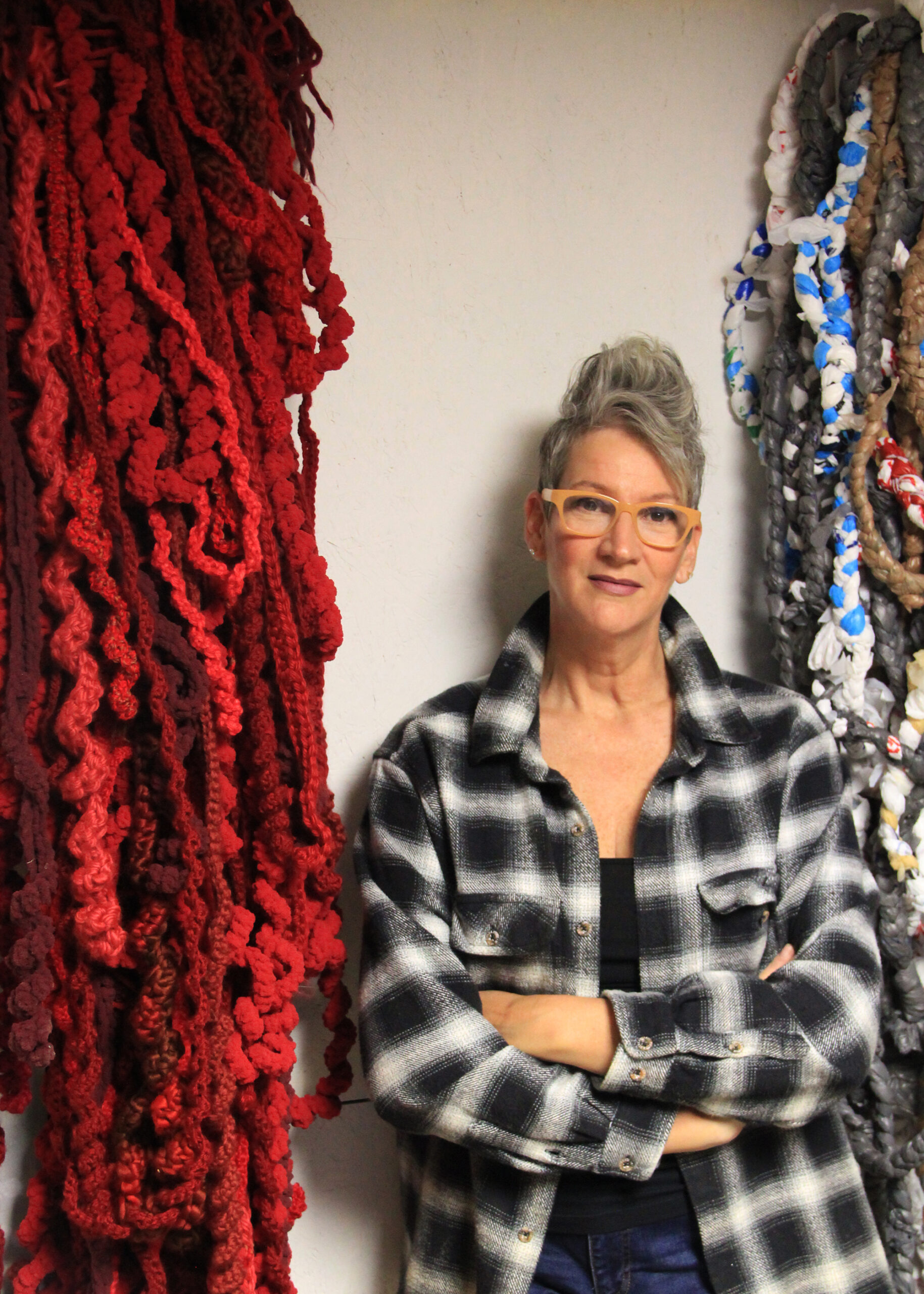 An artist stands with arms folded between two large bundles of chunky fibers hanging from the wall