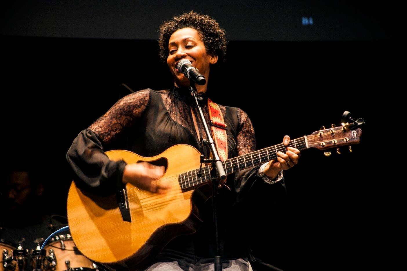 A woman sings into a microphone and plays guitar