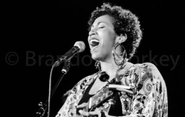 Black and white image of a woman playing acoustic guitar and singing into a microphone