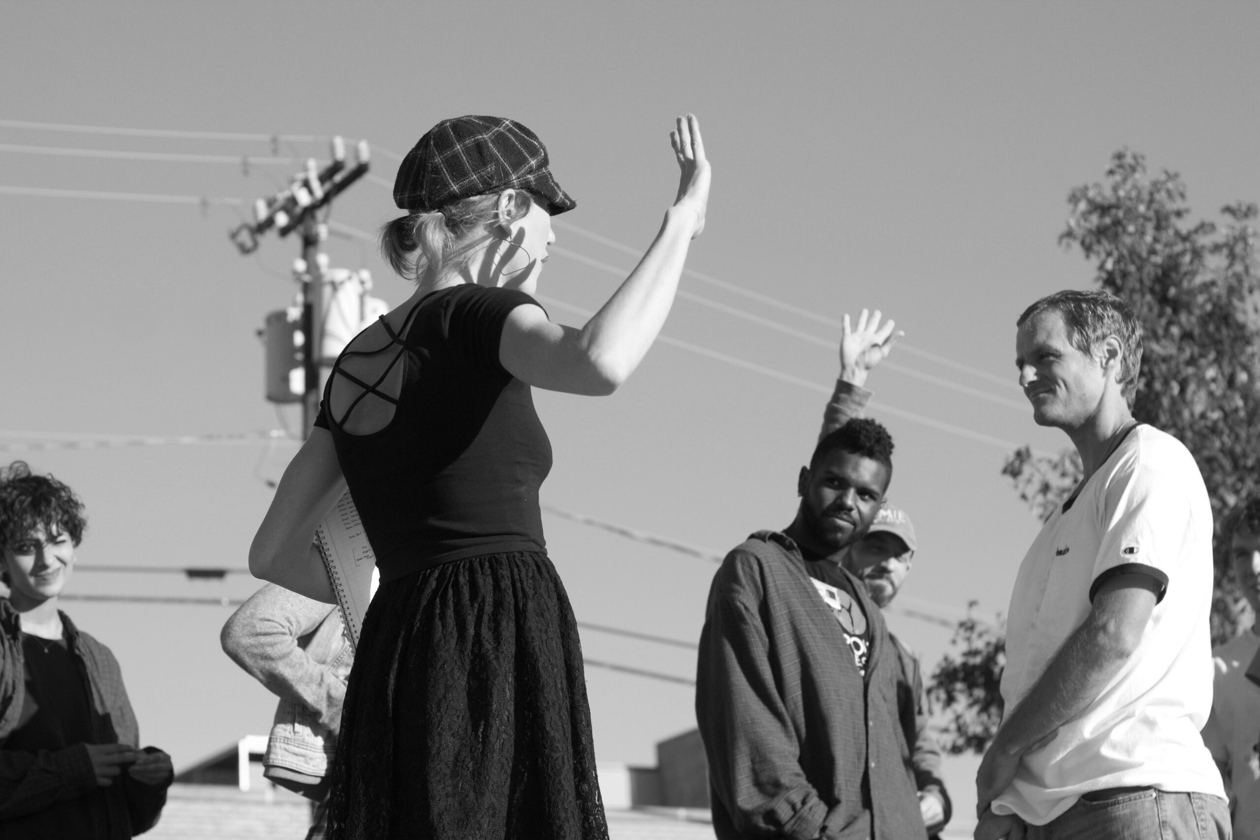 Black and white image taken from below eye level of a woman addressing a group of dancers outside during a rehearsal