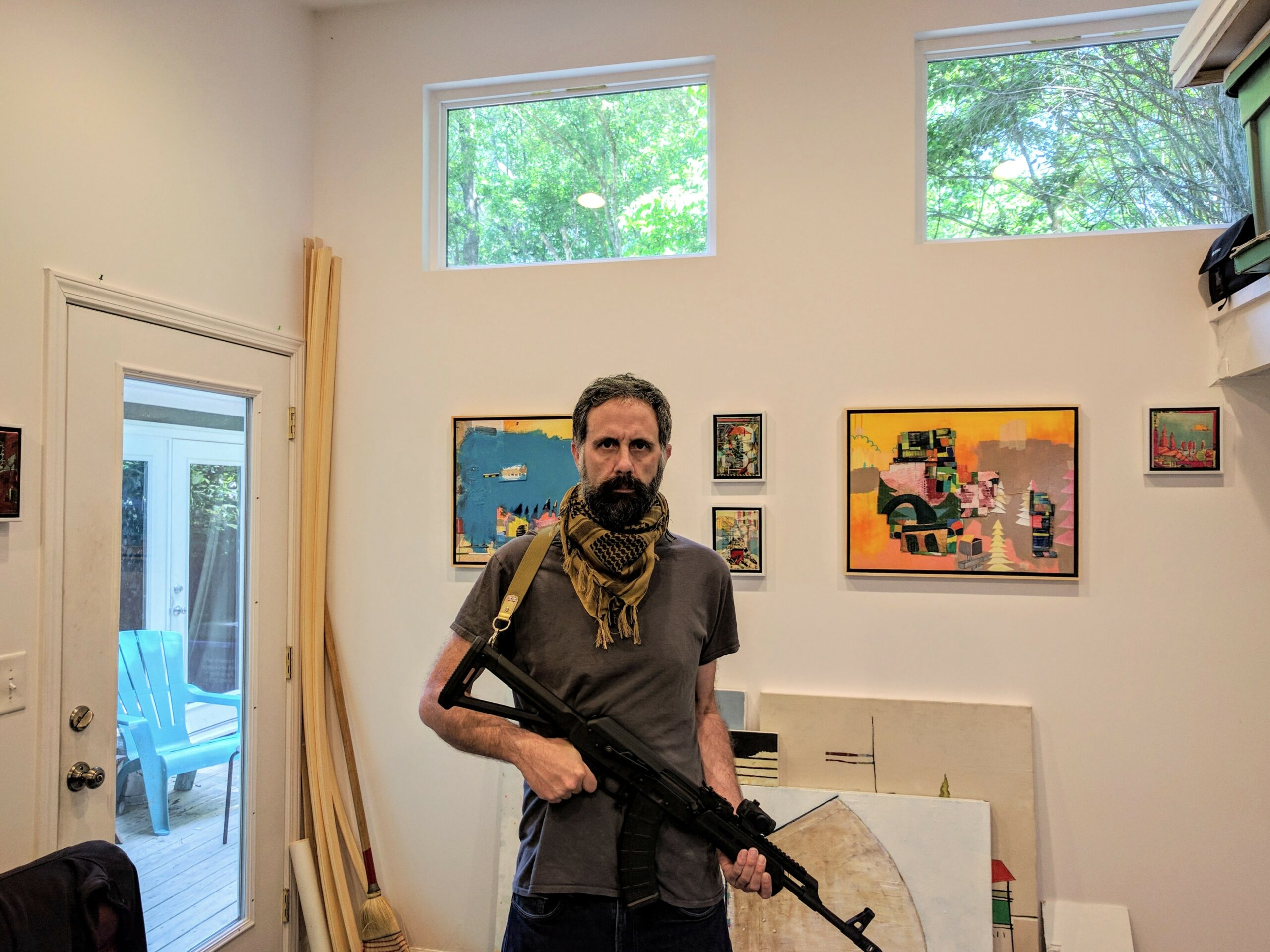 A man stares at the camera holding a rifle. There are paintings on the wall behind him and on the floor leaning against the wall