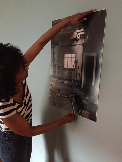 A woman hangs a print of a photograph on a wall