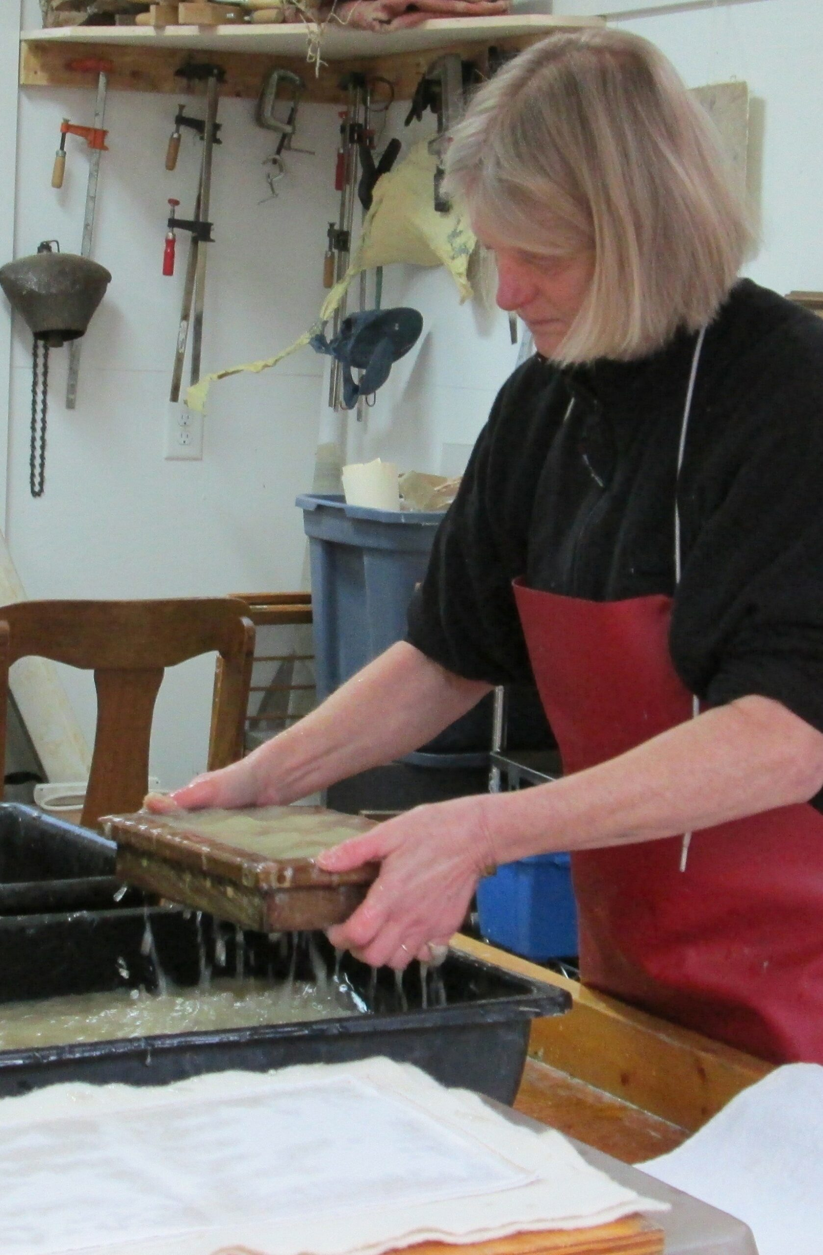 An artist wearing an apron stands at a table and is lifting a block of wood out of a murky liquid