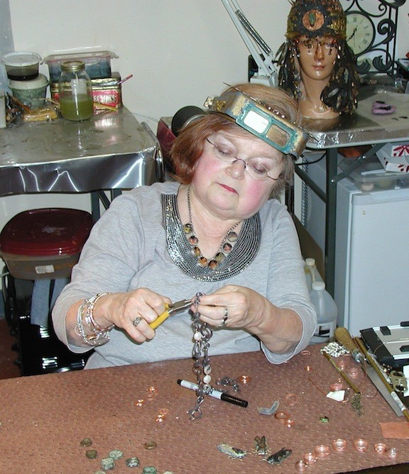 A woman wearing protective goggles on her head uses pliers to adjust a piece of jewelry