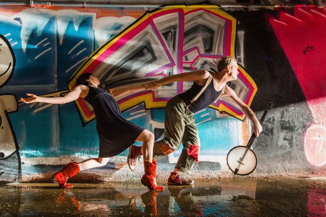 A man and a woman pose as if in movement, gripping hands, past a wall that is heavily graffitied. The man holds a banjo
