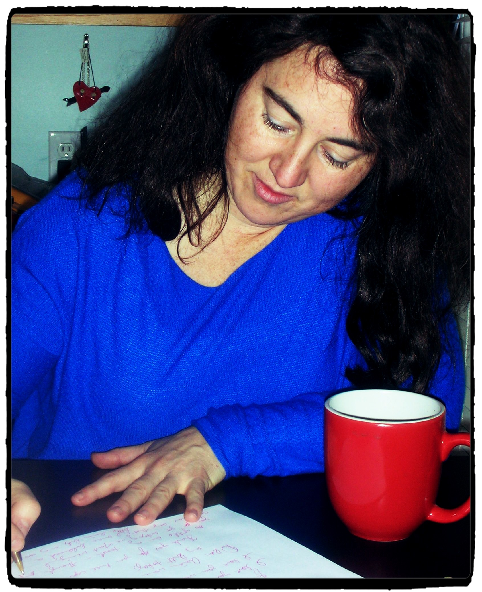 A woman writes on a piece of paper in front of her. There is a coffee mug on the table