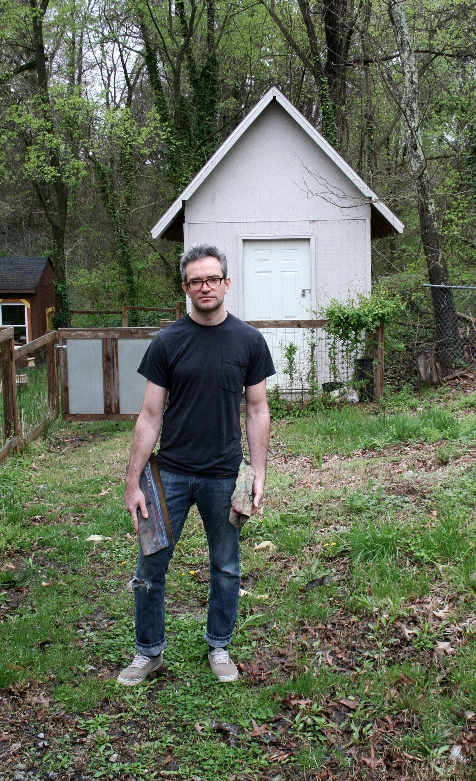 A man stands in a yard holding screen printing equipment. There is a shed behind him