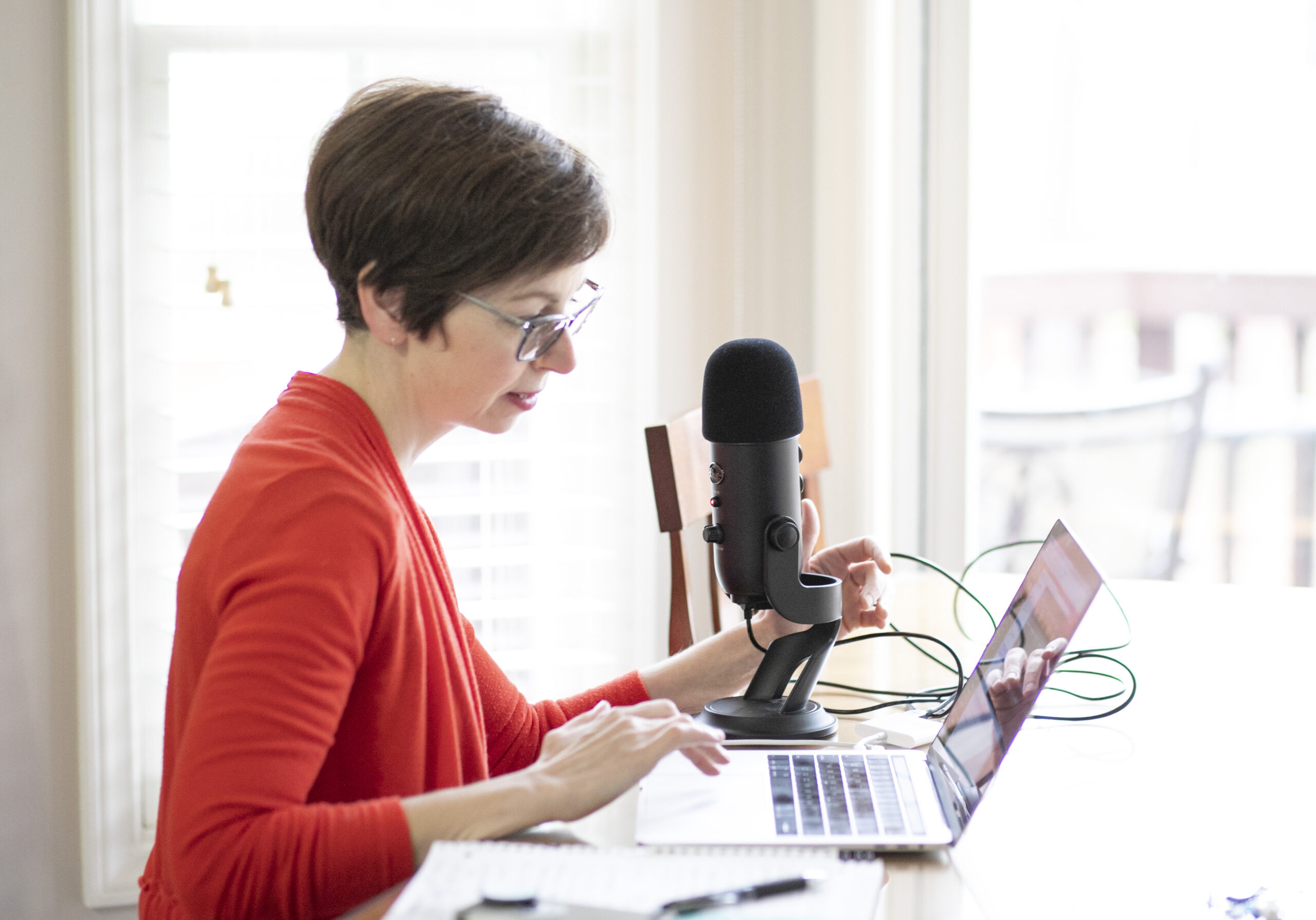 A woman sits in front of a laptop with a microphone