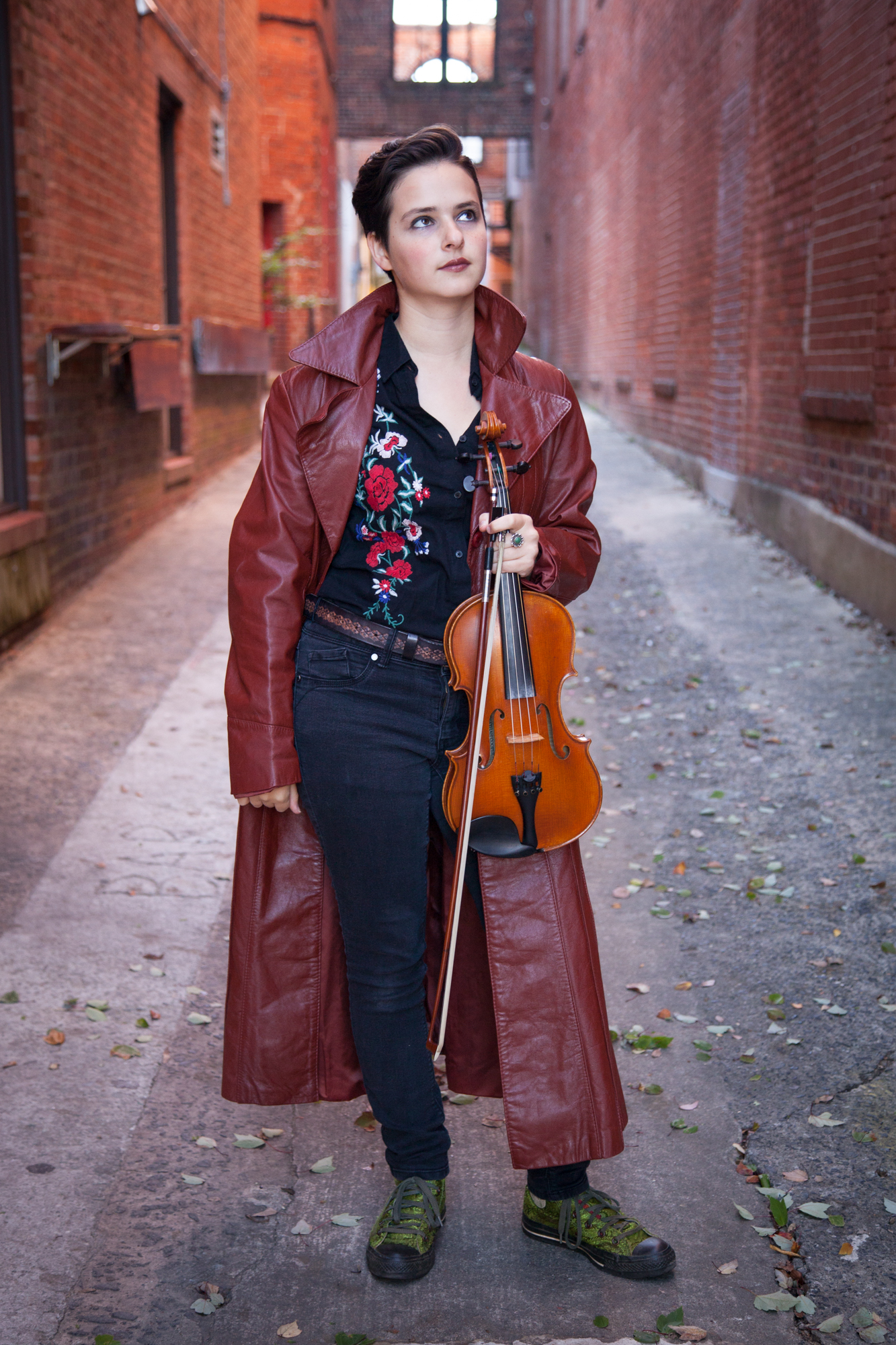A woman stands in a brick alleyway holding a violin and bow. She is looking at the sky