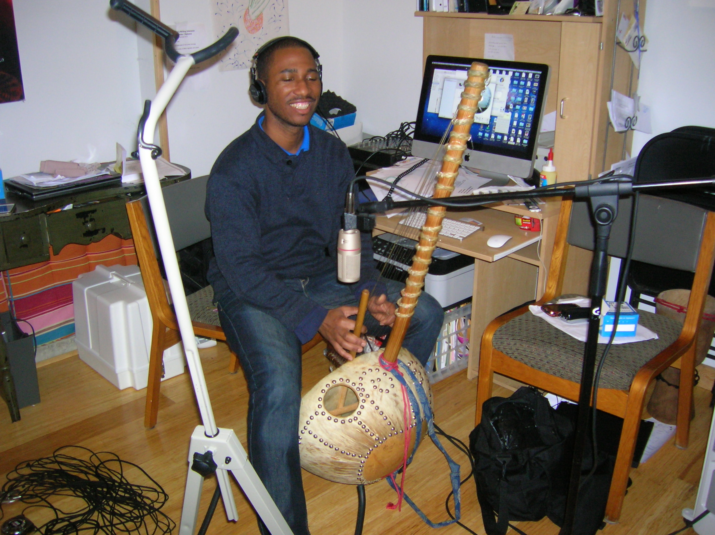 A musician plays a kora in a music studio