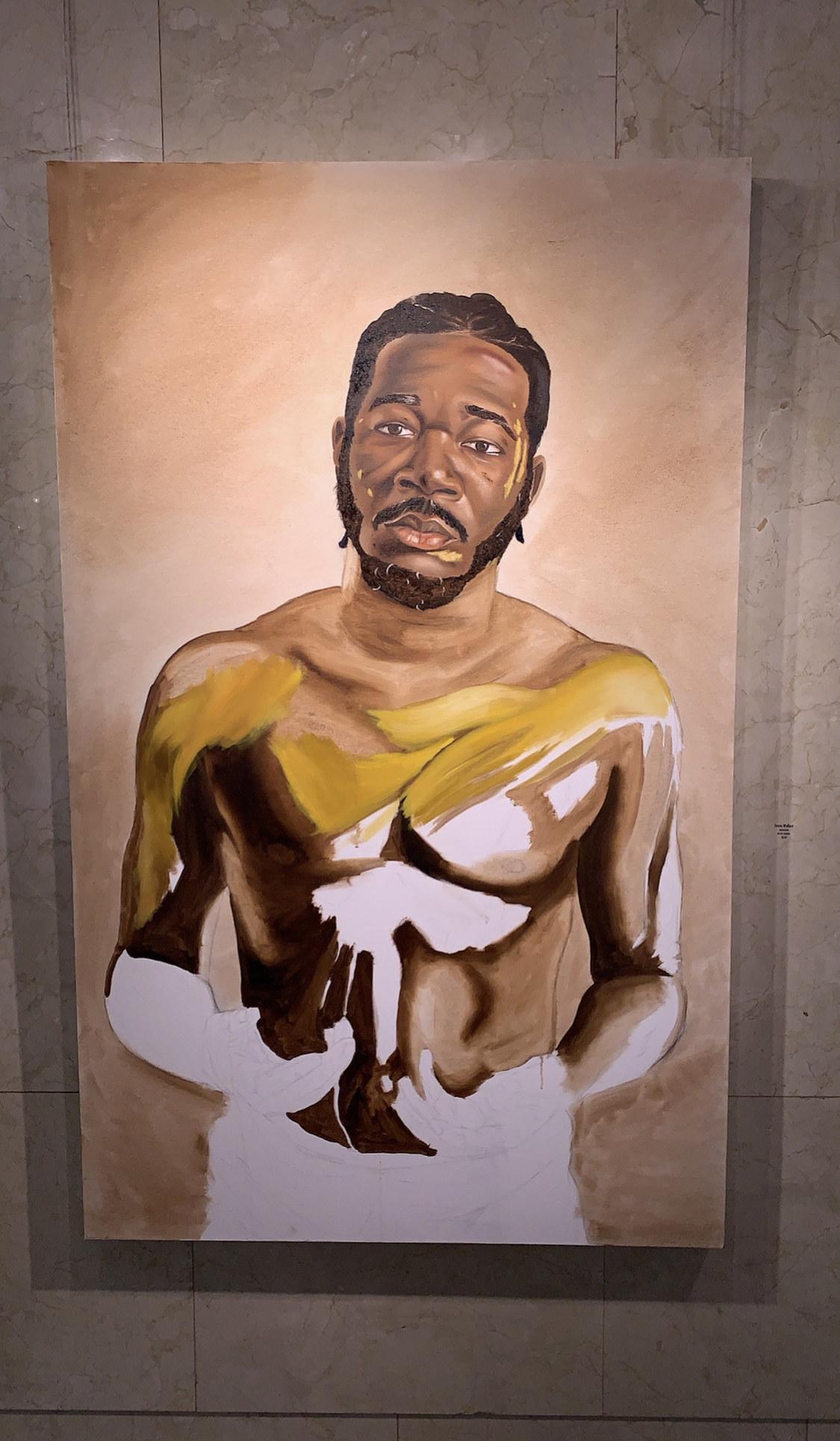 Unfinished painting of a Black man from the waist up. He doesn't have a shirt on and there is a swipe of yellow light across his chest