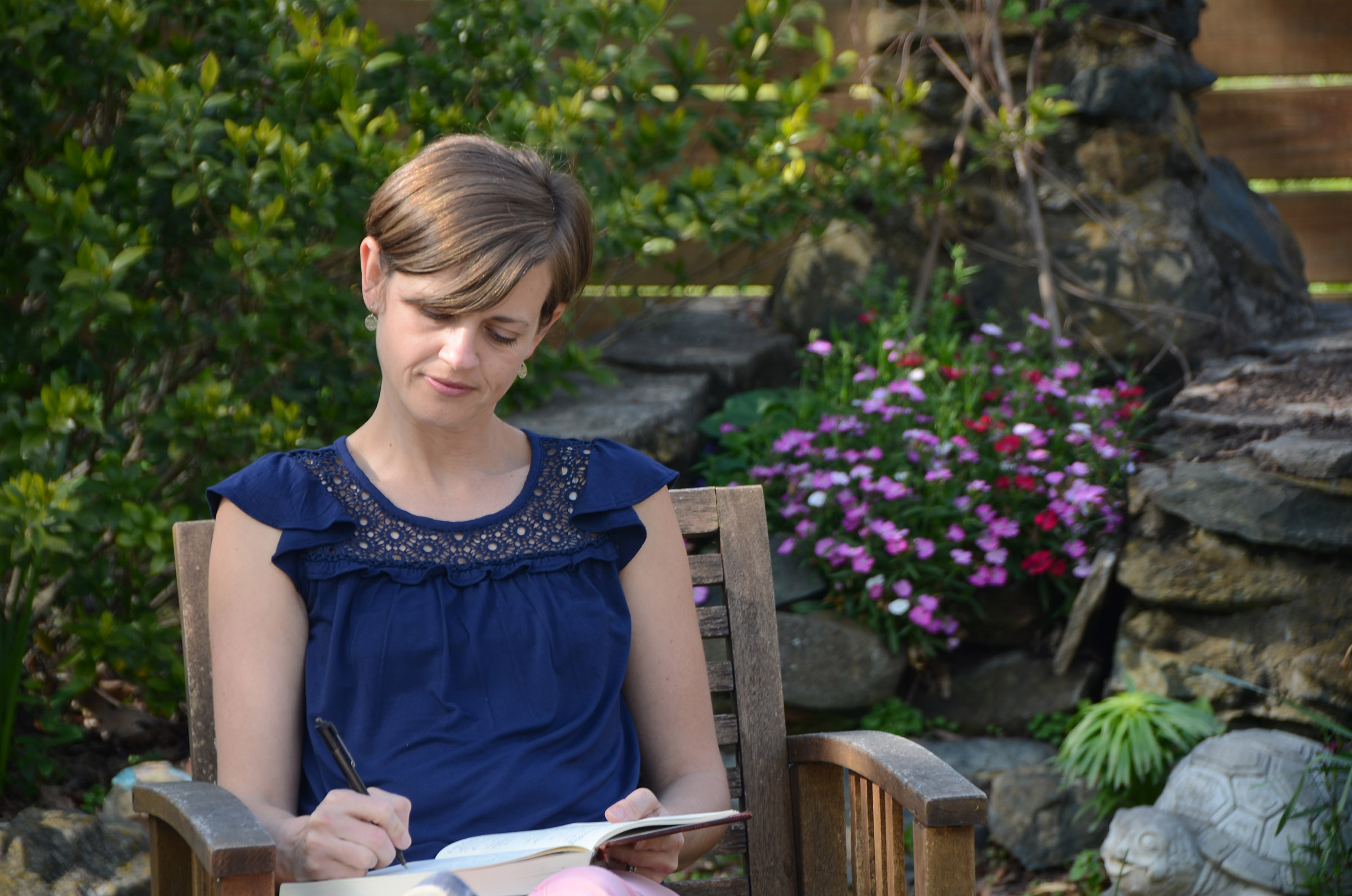 A woman sits on a garden chair writing in a book