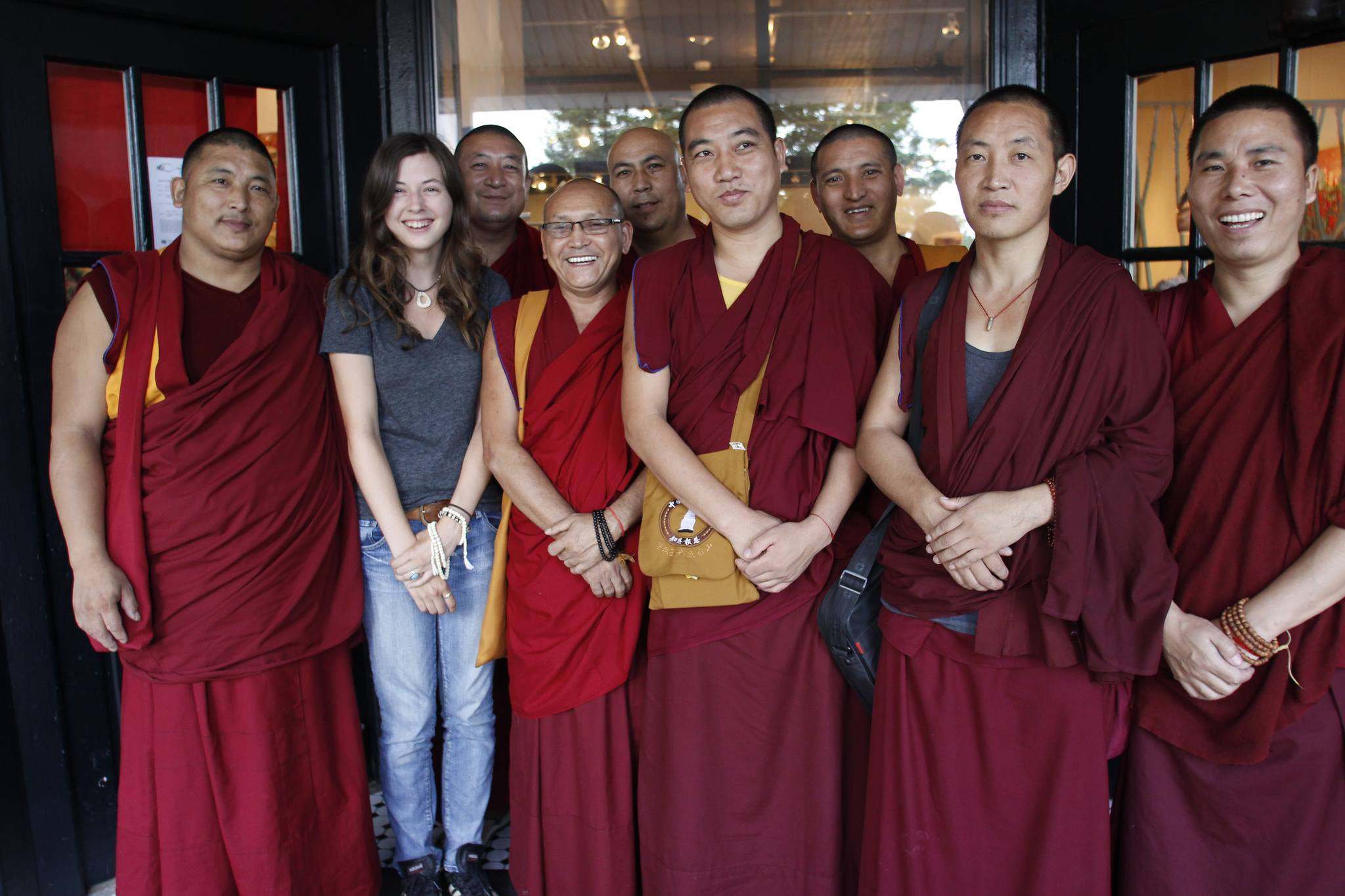 A woman in street clothes stands among a group of Buddhist monks in traditional robes. All are looking at the camera