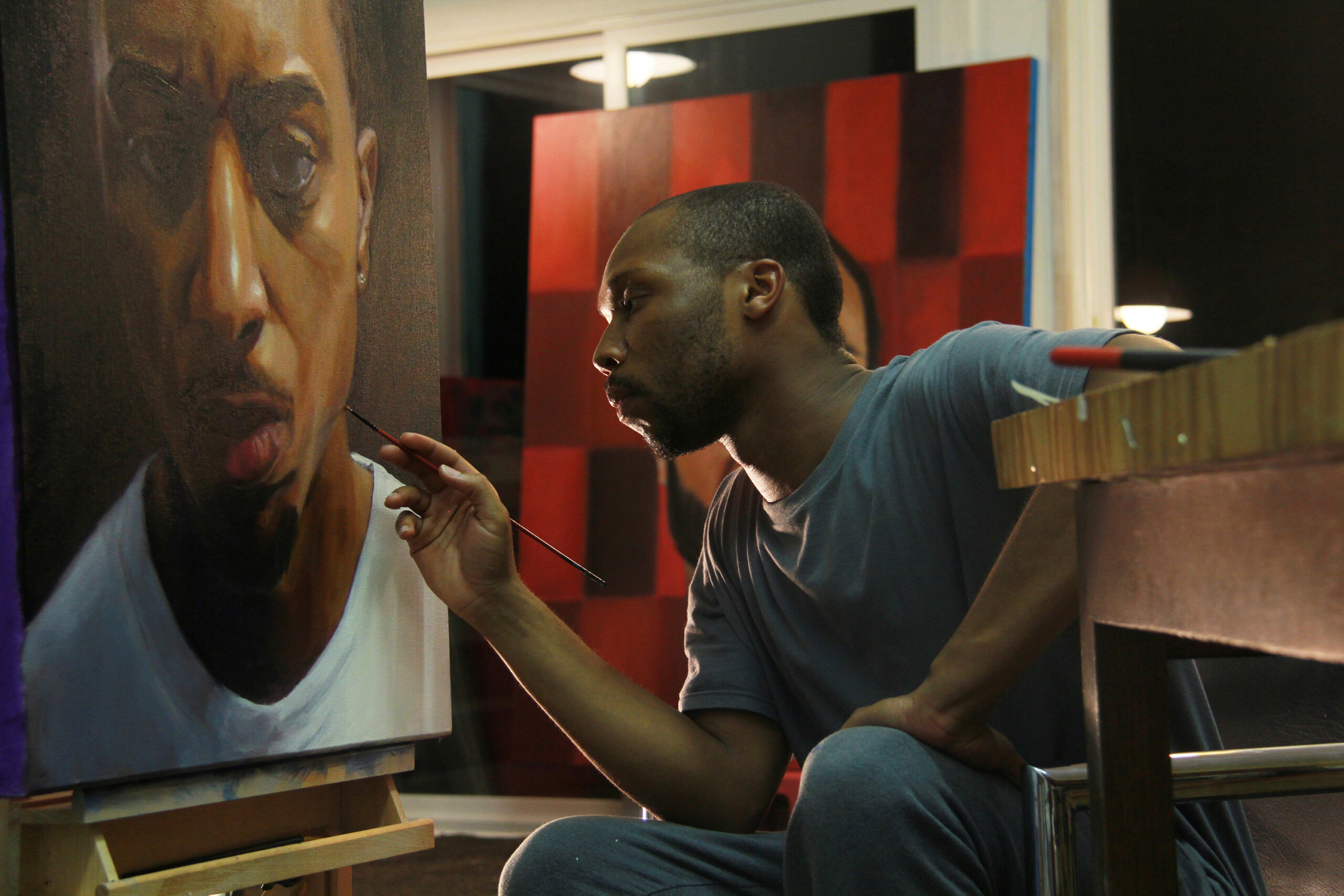 An artist crouches in front of a large portrait of a Black man and works on it with a small paintbrush