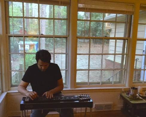 A man sits at a stringed instrument in front of a wall of windows