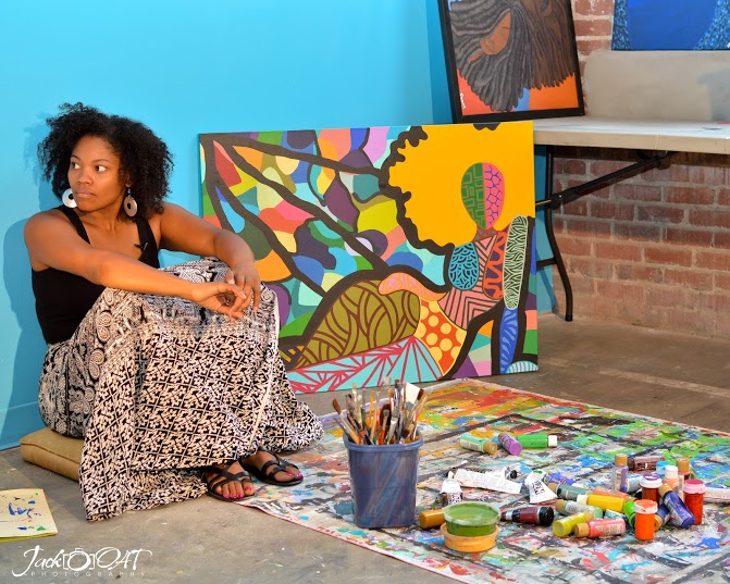 An artist sits on a cushion on the ground with painting supplies in front of her and some finished canvasses behind