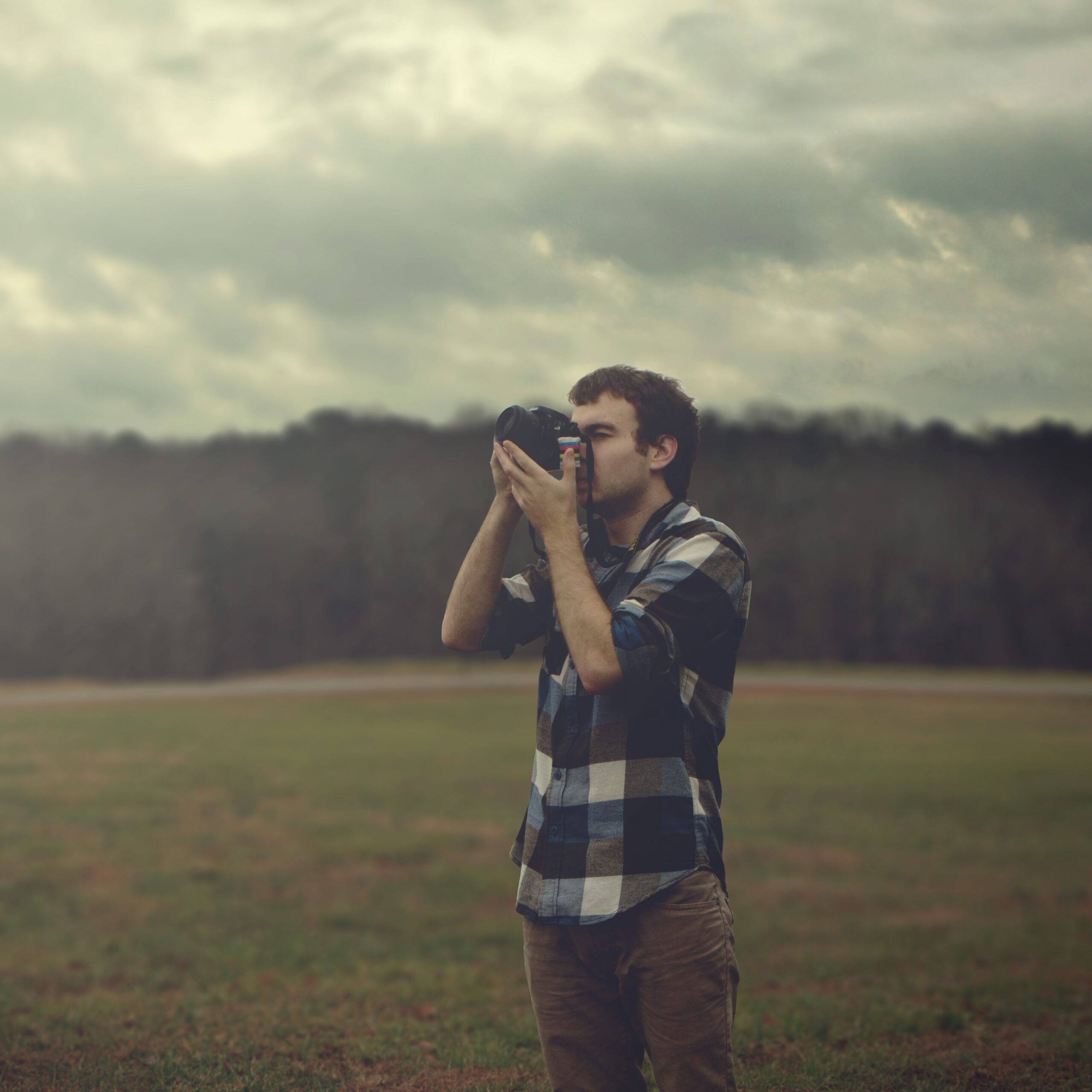 A man stands in a field and takes a photograph with a digital camera