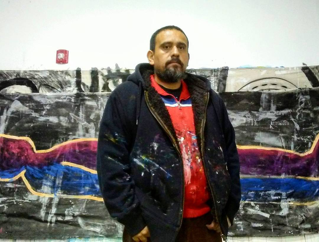 A man looks solemnly at the camera standing in front of a large graffitied wall mural