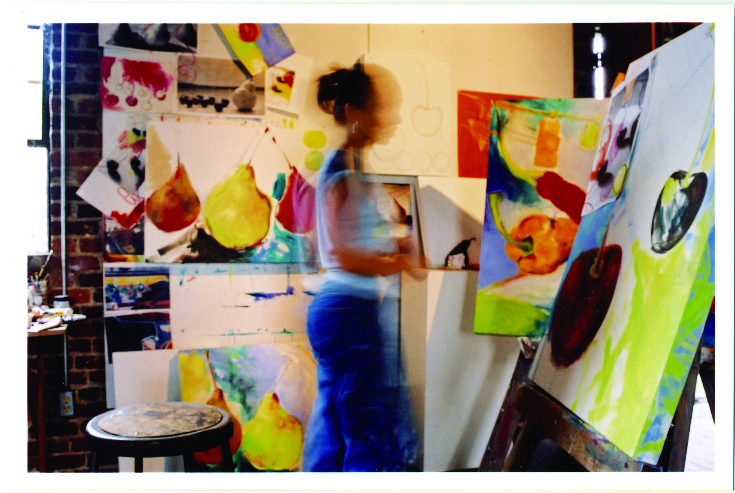 Blurry image of a woman walking through an art studio crowded with paintings