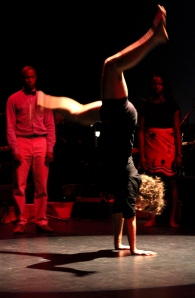 On a dark stage with a red wash someone does a cartwheel in the foreground while two people watch in the background