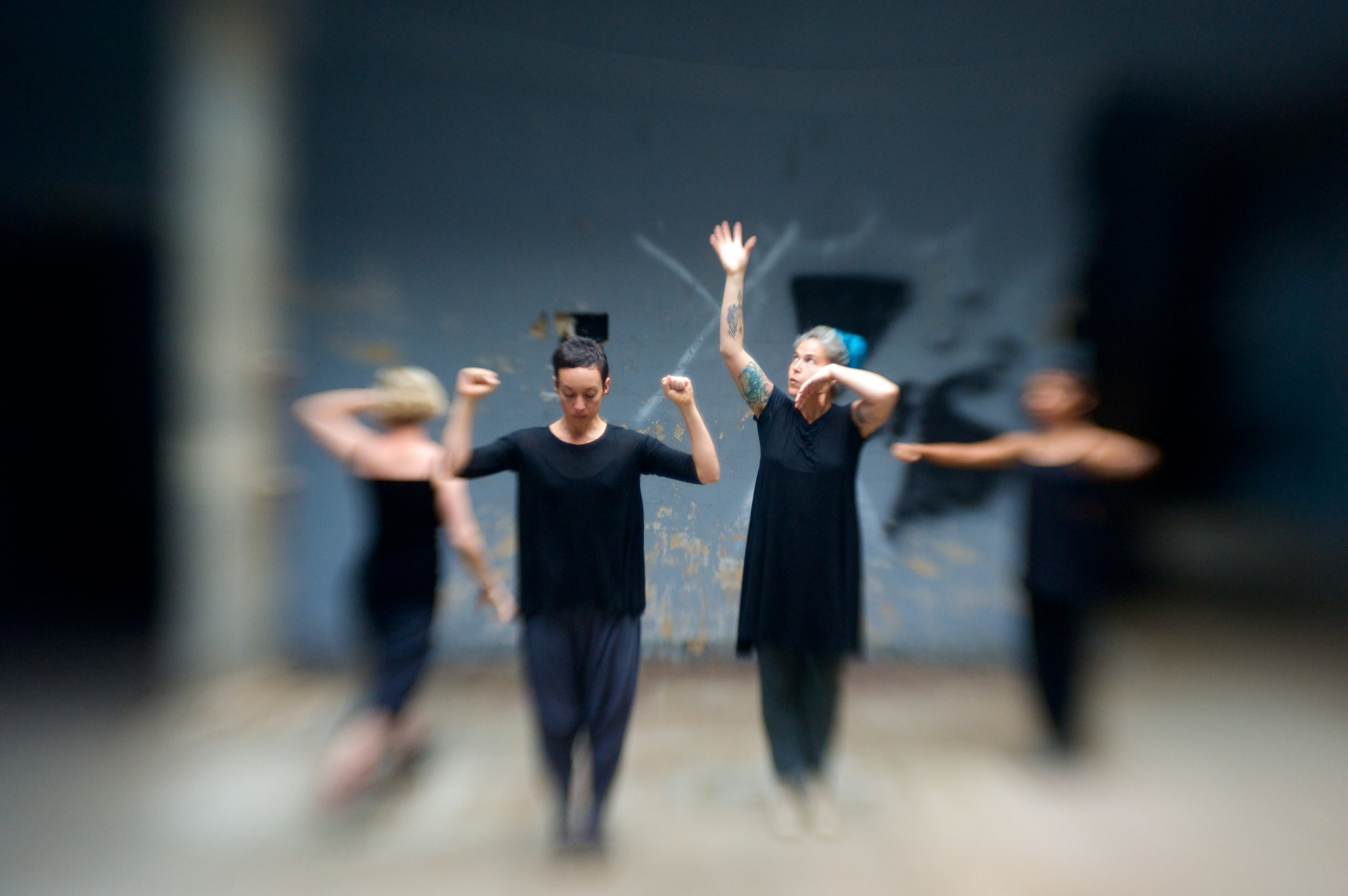 Four dancers perform. The image has a very small area of focus in the middle and gets very out of focus at the edges