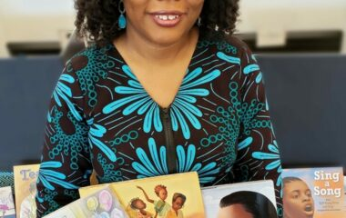 Headshot of a woman holding children's books