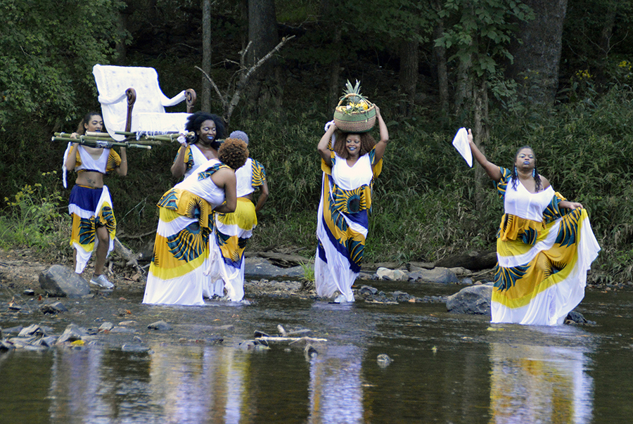 Six women in flowing, brightly patterned dresses wade in a river. They move in a procession. Several women hoist a white upholstered chair over their shoulders, and a smiling woman balances a basket on her head.